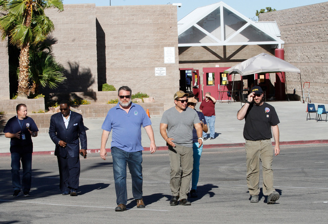Officials go to attend a news conference in front of Johnson Junior High School in Las Vegas, Sunday, Sept. 11, 2016. School officials announced Sunday that Monday classes at the school will be ca ...
