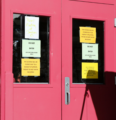 Signs are seen on the door of Johnson Junior High School in Las Vegas, Sunday, Sept. 11, 2016. School officials announced Sunday that Monday classes at the school will be canceled while officials  ...