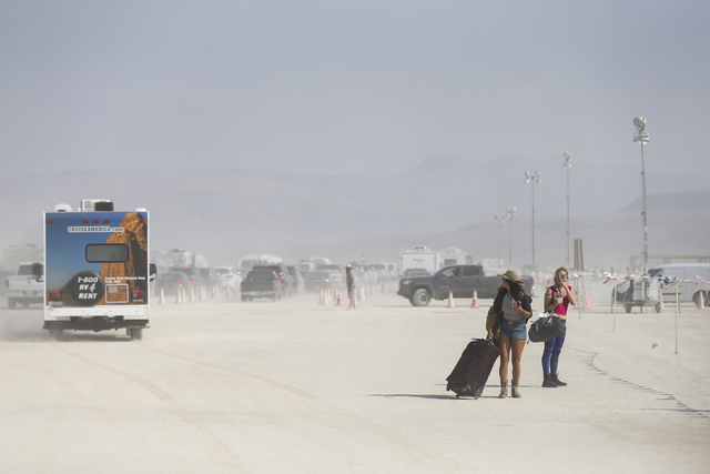 Attendees walk with luggage towards the entrance to Burning Man at the Black Rock Desert north of Reno on Tuesday, Aug. 30, 2016. Chase Stevens/Las Vegas Review-Journal Follow @csstevensphoto