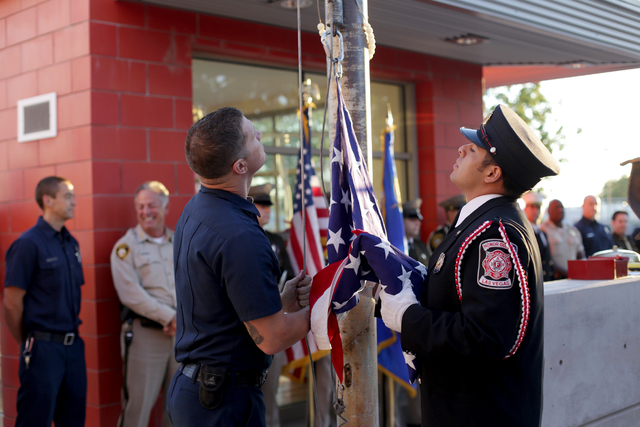 """Firefighter Josh Abston and Las Vegas Fire Department Honor Guard Mario Lueda prepare the flag at the 9/11 """"Tolling of the Bells"""" ceremony at Fire Station Five on Sunday, Sept. 11, 2016, in Las Ve ..."""