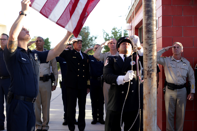"""Firefighter Josh Abston and Las Vegas Fire Department Honor Guard Mario Lueda raise the flag to half-mast at the 9/11 """"Tolling of the Bells"""" ceremony at Fire Station Five on Sunday, Sept. 11, 2016 ..."""