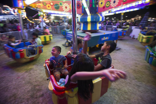 Young carnival-goers take evening spin on an amusement ride during the San Gennaro Feast at Craig Ranch Regional Park in North Las Vegas on Saturday, Sept. 17, 2016. (Richard Brian/Las Vegas) Revi ...