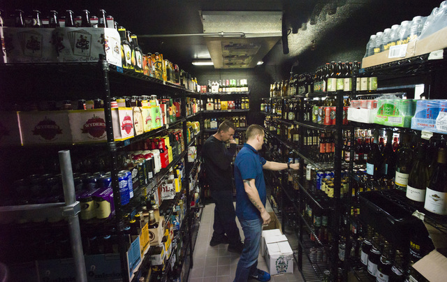 World of Beer area director and franchise consultant Bryan Macina, right, walks through the cooler at World of Beer during the restaurant's opening day at the Galleria at Sunset mall in Henderson  ...