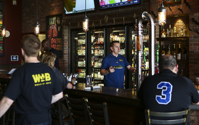 World of Beer area director and franchise consultant Bryan Macina, center right, brings out a plate of food at World of Beer during the restaurant's opening day at the Galleria at Sunset mall in H ...