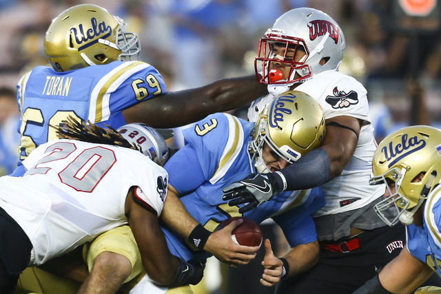 UNLV players, including linebacker LaKeith Walls (20), take down UCLA Bruins quarterback Josh Rosen (3) during a football game at the Rose Bowl in Pasadena, Calif. on Saturday, Sept. 10, 2016. UCL ...