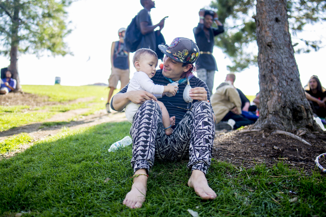 """Killian, an infant raised by his parents along with a community that dwells at Common Park in Denver Colorado, his held by his father, Snoopy Thursday, Sept. 1, 2016.  """"I have found such  ..."""
