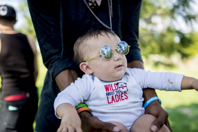 Killian, an infant raised by his parents along with a community that dwells at Common Park in Denver Colorado, is swung by a friend Thursday, Sept. 1, 2016. Elizabeth Page Brumley/Las Vegas Review ...
