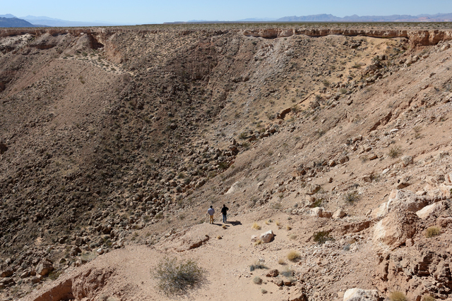 UNLV student Jose Amaya and professor Eric Strain of Assemblage Studio gaze across the open space from the north side of Double Negative, an earth sculpture by Michael Heizer on Mormon Mesa just n ...