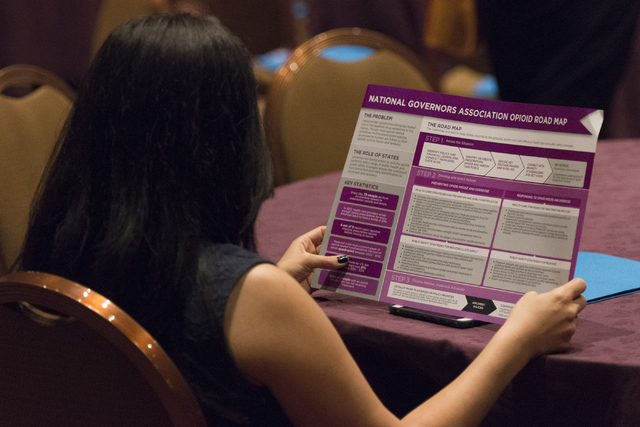 A woman views the National Governors Association Opioid Road Map during Gov. Brian Sandoval's Prescription Drug Abuse Prevention Summit at MGM Grand hotel-casino in Las Vegas, Wednesday, Aug. 31,  ...