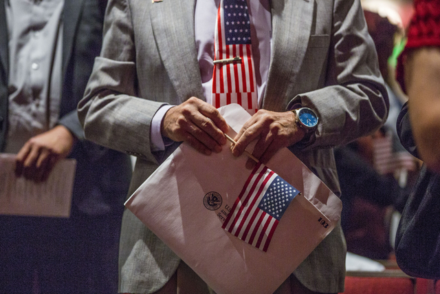A man holds his packet of citizenship with a small flag during a naturalization ceremony at Cashman Field Thursday, Sept. 22, 2016, in Las Vegas. (Elizabeth Page Brumley/Las Vegas Review-Journal)  ...