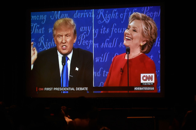 Presidential candidates Donald Trump and Hillary Clinton appear on a video monitor at debate watch event at UNLV Monday, Sept. 26, 2016, in Las Vegas. Several hundred college, middle and high scho ...