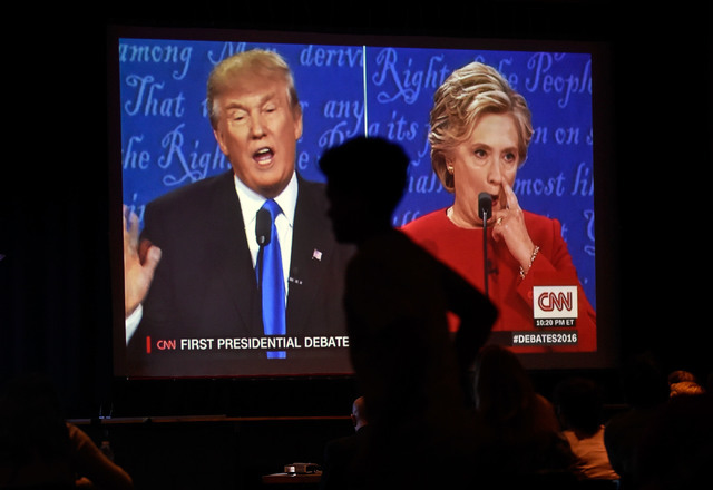 A person walks by a video monitor as presidential candidates Donald Trump and Hillary Clinton appear on a screen at debate watch event at UNLV Monday, Sept. 26, 2016, in Las Vegas. Several hundred ...