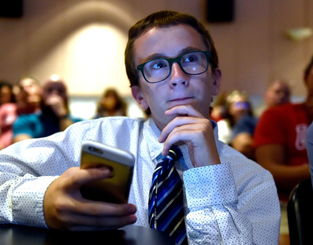 Palo Verde High School student Justin Hazleton uses his mobile device as he watches the presidential debate at UNLV Monday, Sept. 26, 2016, in Las Vegas. Several hundred college, middle and high s ...