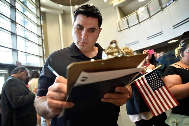 Israel DeLeon of Mexico fills out a voter registration application after becoming a United States citizen at a naturalization ceremony at Nevada State College Friday, Aug. 19, 2016, in Henderson.  ...