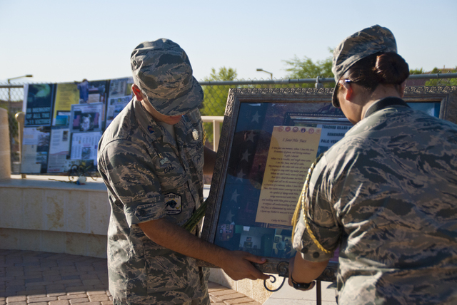 Alfredo Diaz, left, and Sukyeong Kim, members of the Palo Verde High School Air Force JROTC, prepare to honor the victims of the 9/11 attacks with a flag rededication ceremony at the Barbara Edwar ...
