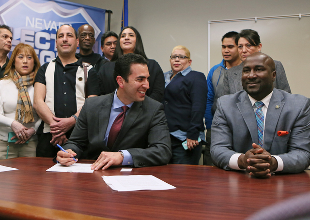 Democratic state Sen. Ruben Kihuen, seated left, laughs with Las Vegas City Councilman Ricki Barlow, right, as he fills out paperwork to file with the Secretary of State's office for the 4th Congr ...
