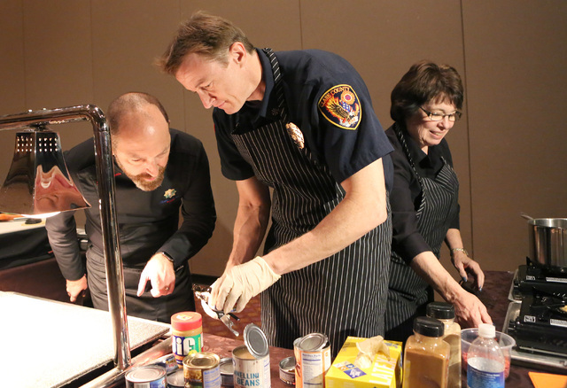 Chef Steve Benjamin, left, Clark County Fire Deputy Chief, John Steinbeck, and Commissioner, Mary Beth Scow, right, prepare food during the third annual Emergency Preparedness Kit Cook-Off competi ...