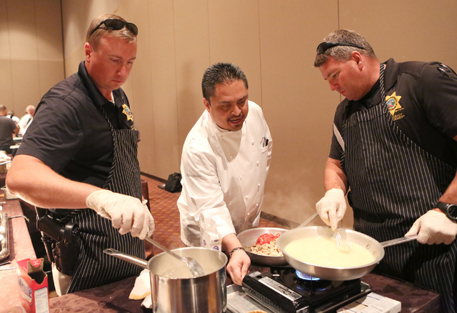 Metro Detectives, Jason Moyer, left, and Patrick Burke, right, prepare food during the third annual Emergency Preparedness Kit Cook-Off competition on Thursday, Sept. 15, 2016, at the MGM hotel-ca ...