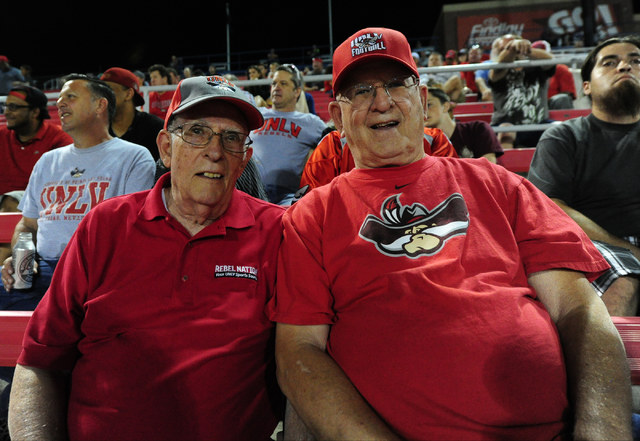 Long time UNLV season ticket holders Len Schweitzer, left, and Tom Kemp watch the Rebels take on the Idaho Vandals in the first half of their NCAA college football game at Sam Boyd Stadium in Hend ...