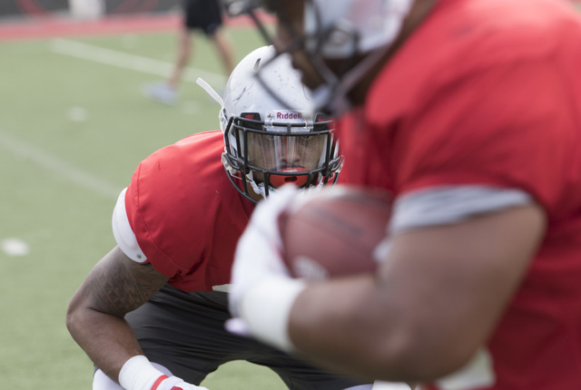 UNLV defensive end Jeremiah Valoaga, left, keeps his eyes on the ball while on a scrimmage during team practice at the Bill 'Wildcat' Morris Rebel Park field on Tuesday, Sept. 20, 2016. (Richard B ...