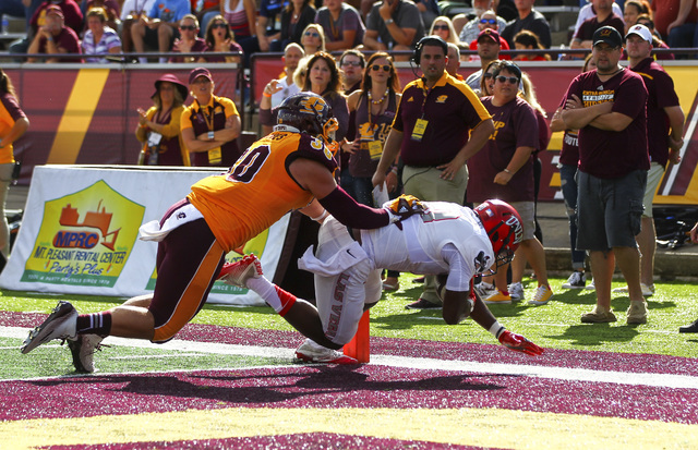 UNLV wide receiver Darren Woods Jr. (10) scores a touchdown as Central Michigan linebacker Alex Briones (30) defends during a football game at Kelly/Shorts Stadium in Mount Pleasant, Mich. on Satu ...