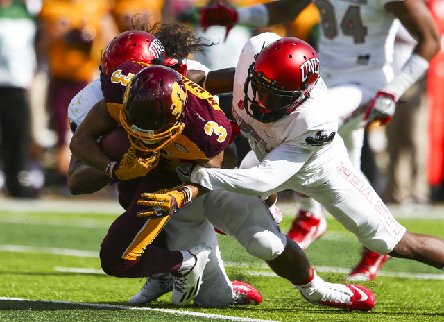 Central Michigan wide receiver Mark Chapman (3) is tackled by UNLV linebacker Tau Lotulelei (55), left, and defensive back Darius Mouton (21) during a football game at Kelly/Shorts Stadium in Moun ...