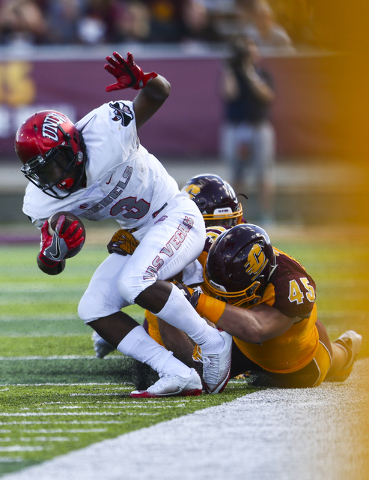 UNLV running back Lexington Thomas (3) is taken down by Central Michigan defense, including defensive lineman Joe Ostman (45), during a football game at Kelly/Shorts Stadium in Mount Pleasant, Mic ...