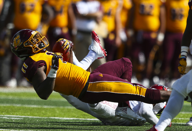 Central Michigan running back Jahray Hayes (11) is tripped up by UNLV during a football game at Kelly/Shorts Stadium in Mount Pleasant, Mich. on Saturday, Sept. 17, 2016. Central Michigan won 44-2 ...