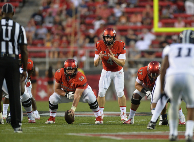 UNLV Rebels quarterback Johnny Stanton (4) takes a snap from offensive lineman Will Kreitler (58) in the first quarter during the UNLV Jackson State football game in Las Vegas on Thursday, Sept. 1 ...