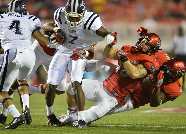 Jackson State Tigers defensive back Zavian Bingham (7),  center, is brought down by UNLV Rebels linebacker Bailey Laolagi (48) and linebacker Brian Keyes (5) following a kick return in the first h ...