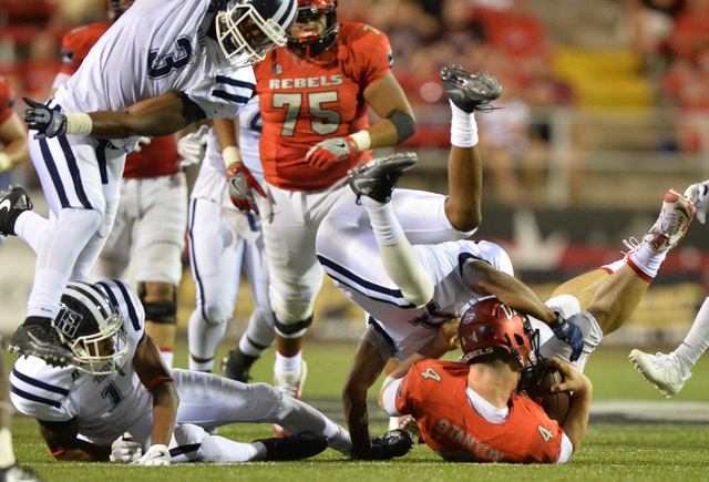 UNLV Rebels quarterback Johnny Stanton (4) is sacked by Jackson State Tigers defense back Derrick Bobo (11) in the third quarter during the UNLV Jackson State football game in Las Vegas on Thursda ...