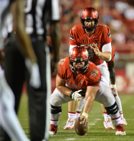 UNLV Rebels quarterback Johnny Stanton (4) takes a snap from offensive lineman Will Kreitler (58) in the third quarter during the UNLV Jackson State football game in Las Vegas on Thursday, Sept. 1 ...
