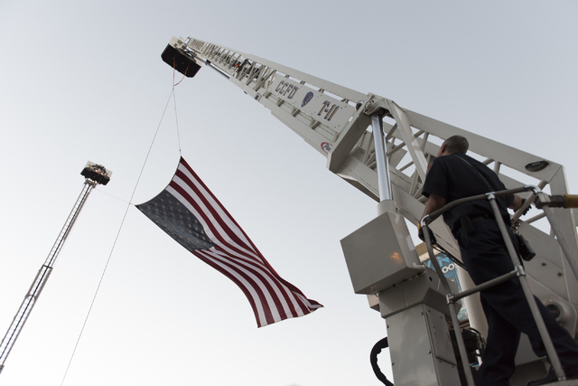 Members of Las Vegas Fire & Rescue and the Clark County Fire Department hoist an american flag prior to a march in downtown Las Vegas, Sunday, Sept. 11, 2016. The annual march honors the lives ...
