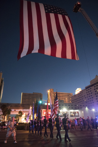 March participants walk under a 50 foot american flag on 3rd Street at Ogden Avenue in downtown Las Vegas, Sunday, Sept. 11, 2016. The annual march honors the lives lost 15 years ago at the World  ...