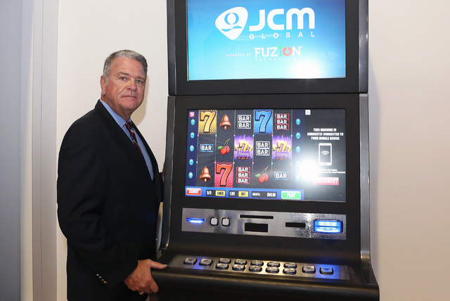 Tom Nieman, vice president of worldwide marketing at JCM Global, poses for a photo next to a slot machine with Fuzion technology, Monday, Sept. 26, 2016, at the Sands Expo and Convention Center. ( ...