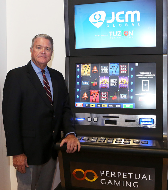 Tom Nieman, vice president of worldwide marketing at JCM Global, poses for a photo next to a slot machine with Fuzion technology, Monday, Sept. 26, 2016, at the Sands Expo and Convention Center.   ...