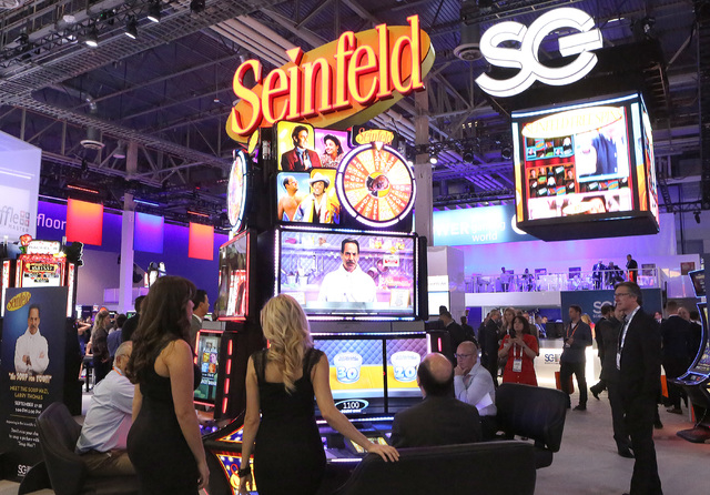 Expo-goers play on a new slot machine based on the American sitcom ғeinfeldӠat Scientific Game booth during the Global Gaming Expo, Tuesday, Sept. 27, 2016, at the Sands Expo and Conve ...
