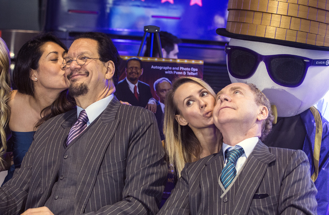 Penn Jillette, left, and Teller get kissed by models while sign autographs during the debut of the Penn & Teller slot machine in the Everi booth during Global Gaming Expo at the Las Vegas Sand ...
