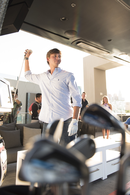 Shriners Hospitals for Children Open defending champion Smylie Kaufman changes clubs in-between hitting golf balls at Topgolf's driving range during a media day for the tournament in Las Vegas, Mo ...