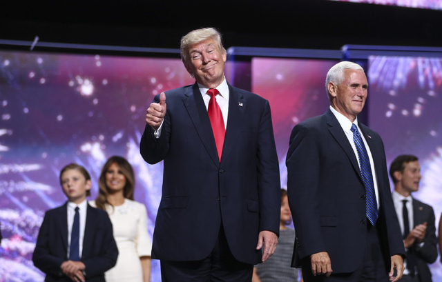 Republican presidential nominee Donald Trump celebrates with running mate Mike Pence at the conclusion of the Republican National Convention at Quicken Loans Arena in Cleveland on Thursday, July 2 ...