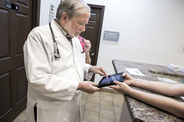 Dr James Gabroy sign his name on a personal device in is office at 1535 W. Warm Springs Road in Henderson on Wednesday, Aug. 31, 2016.  (Jeff Scheid/Las Vegas Review-Journal) Follow @jeffscheid