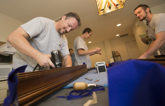 President of On Cue Billiards Kevin Knoke, from left, with employees Austin Younger and Darcy McDonald as they work on leveling and felting the pool table of customer Jim MacMillan at MacMillan's  ...