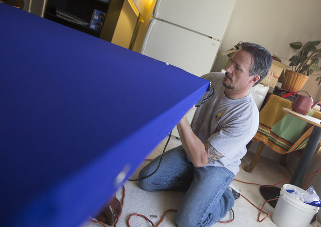 President of On Cue Billiards Kevin Knoke staples on a new felt to the pool table of his customer Jim MacMillan at MacMillan's residence in Las Vegas on Monday, Sept. 26, 2016. (Richard Brian/Las  ...