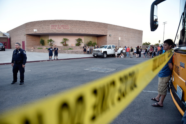 Parents wait for their children to be released from Johnson Junior High School after a hazardous material, suspected to be mercury, was found in the schoolճ gymnasium Wednesday, Sept. 7, 201 ...