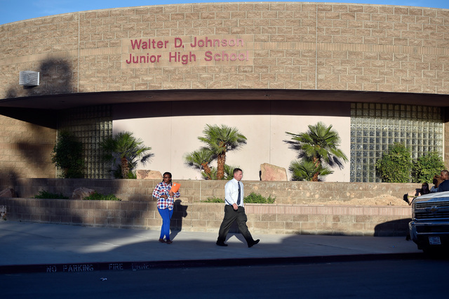 A student walks with an administrator after being released from Johnson Junior High School Wednesday, Sept. 7, 2016, in Las Vegas. A hazardous material, suspected to be mercury, was found in the s ...