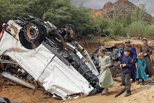 People walk pass damaged vehicles swept away during a flash flood in Hildale, Utah, Sept. 15, 2015. At least a dozen people were swept away to their deaths in the fatal flash floods. (Rick Bowmer/AP)