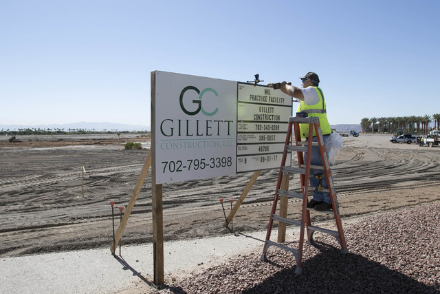 Gillette Construction Manager Brad Seller installs the dust control permit sign at the site of the headquarters and practice facility for Las Vegas's HNL expansion team on Pavilion Center Drive ac ...