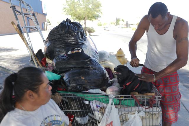 Monica Salas watches her fiancé Carl Albert Graves comb their dog Chico's fur at their encampment behind EZ Pawn on Saturday, Sept. 17, 2016, in Las Vegas. Rachel Aston/Las Vegas Review-Journ ...