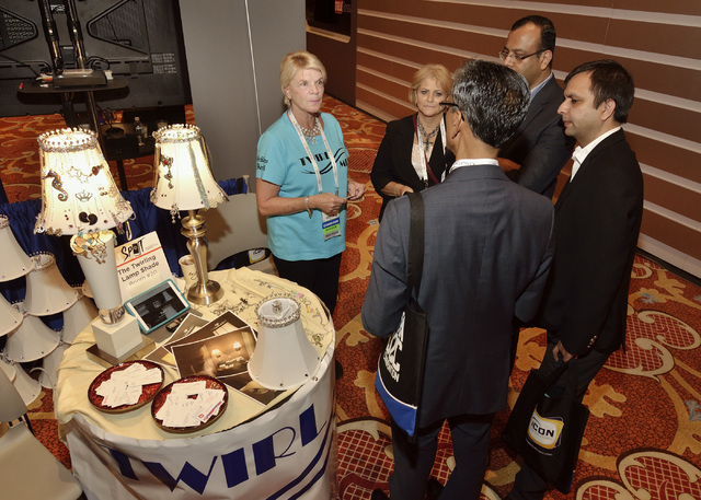 Donna Stokes, left, talks with visitors to her Twirling Lamp Shade booth at the 2016 Electronic Retailing Association D2C Convention in the Wynn Las Vegas on Thursday, Sept. 15, 2016. (Bill Hughes ...