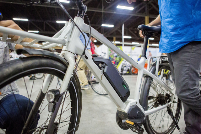 Exhibitors hold an eBbike at the annual Interbike International Bicycle Exposition at the Mandalay Bay Convention Center, Wednesday Sept. 21, 2016, in Las Vegas. (Elizabeth Page Brumley/Las Vegas  ...